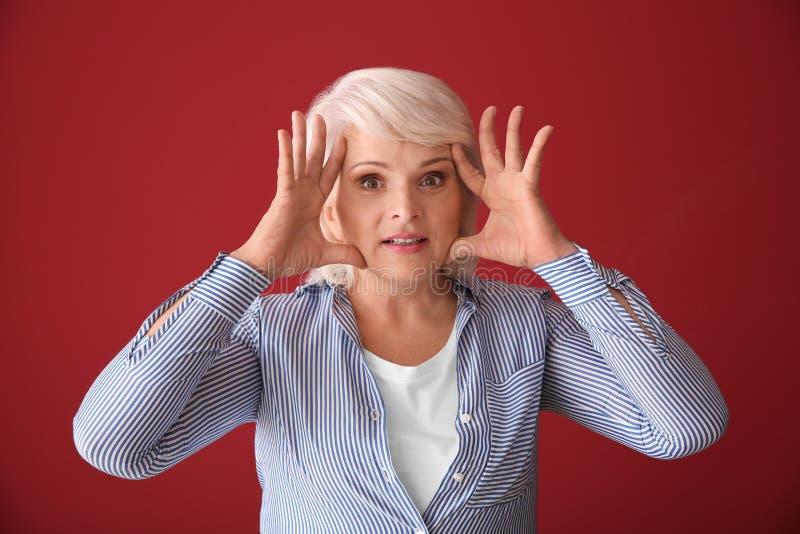 Portrait drôle de femme mûre sur le fond de couleur images stock