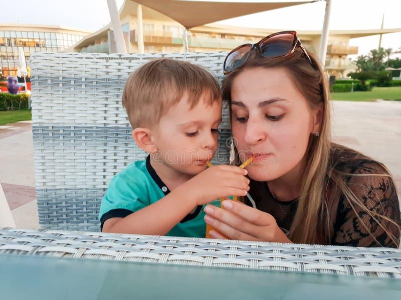 Portrait drôle de jeune mère avec le garçon d'enfant en bas âge buvant du jus d'orange de la paille deux au café de plage image libre de droits