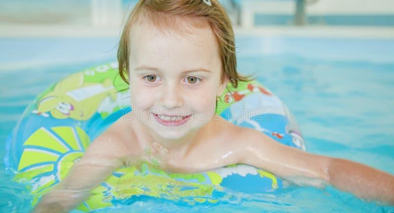 Portrait drôle de la fille mignonne heureuse de petit enfant jouant avec l'anneau coloré dans la piscine images stock