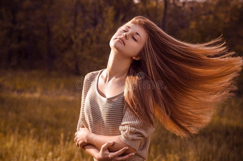 Portrait dramatique d'un thème de fille : portrait d'une belle fille avec des cheveux de vol dans le vent sur un fond dans la for photos stock