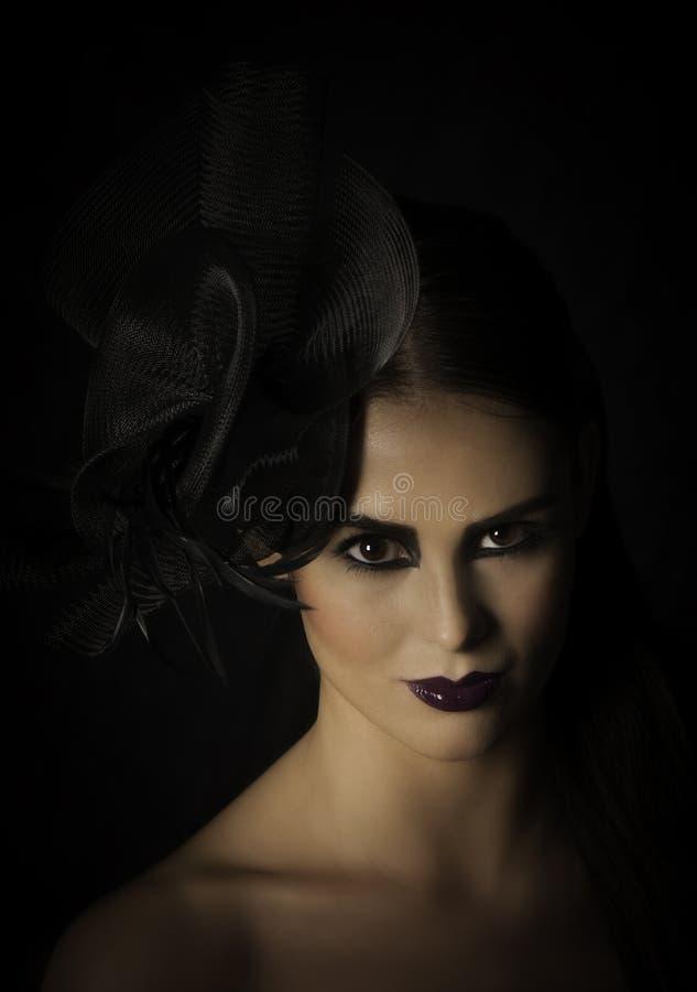 Portrait dramatique de belle femme dans le maquillage foncé avec le chapeau images stock