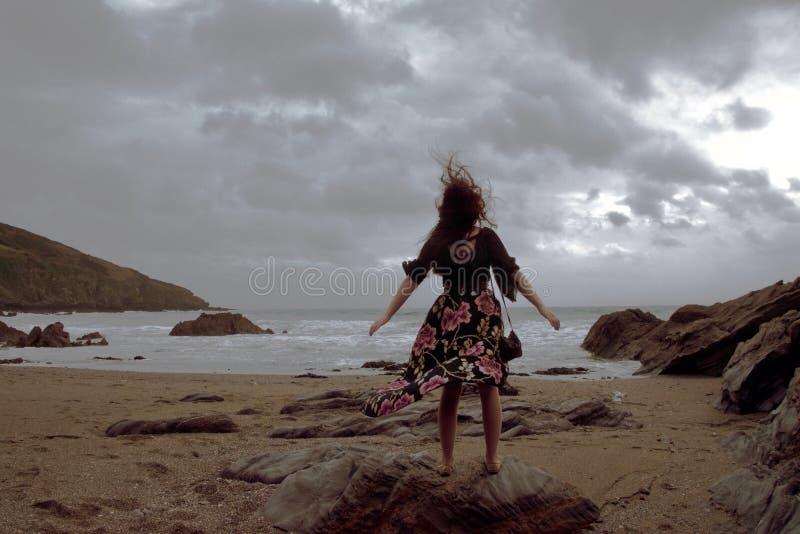 Portrait dramatique de dame aux cheveux longs dans la robe formelle florale sur une plage orageuse image libre de droits