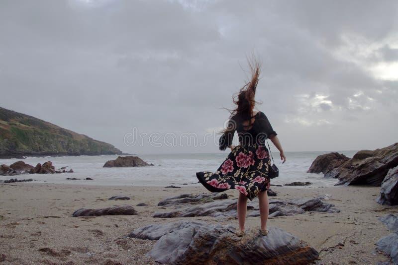 Portrait dramatique de dame aux cheveux longs dans la robe formelle florale sur une plage orageuse images stock