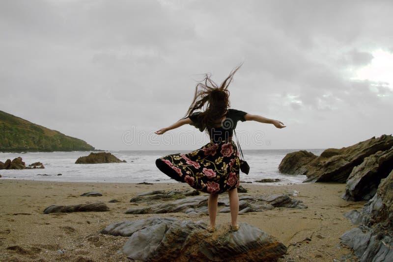 Portrait dramatique de dame aux cheveux longs dans la robe formelle florale sur une plage orageuse avec des bras ouverts images libres de droits