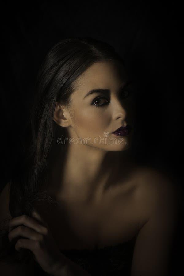 Portrait dramatique de femme d'une chevelure foncée dans le noir photographie stock libre de droits