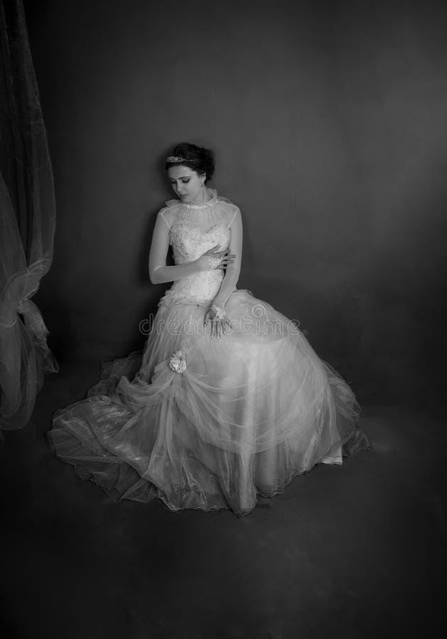 Portrait dramatique de robe de port de vintage de brune, se penchant contre un mur image libre de droits