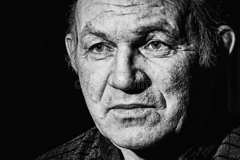 Portrait dramatique noir et blanc d'un homme d'âge de retraite avec des rides sur un fond foncé image stock