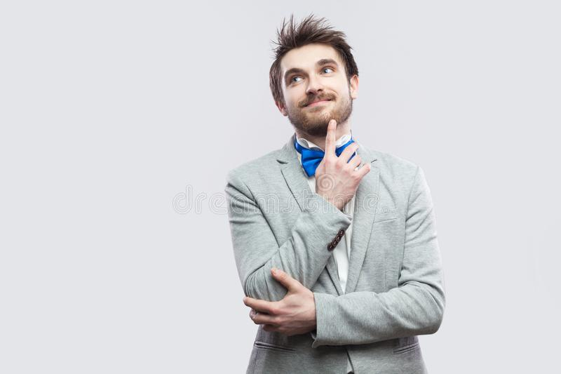 Portrait of dreamful happy handsome bearded man in casual grey suit and blue bow tie standing and looking away, smiling and royalty free stock photo