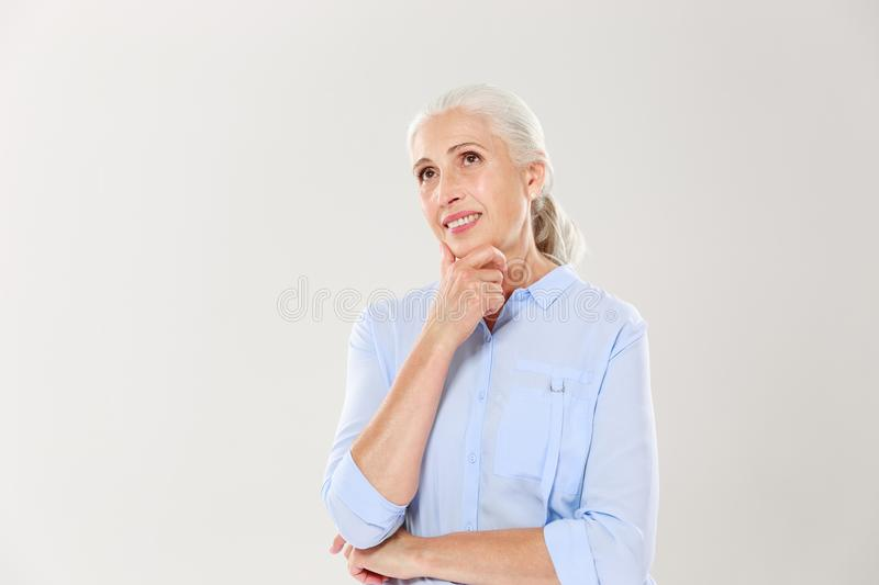 Portrait of dreaming cheerful old lady, touching her chin, looking aside stock images