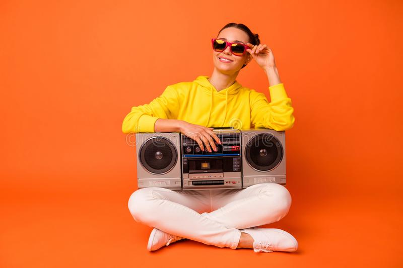 Portrait of dreaming lady touching eyewear eyeglasses sitting with boom box isolated over orange background. Portrait of dreaming lady, touching eyewear royalty free stock photos