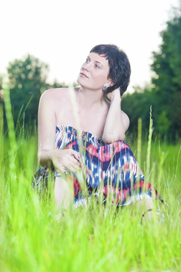 Portrait of Dreaming and Relaxing Caucasian Brunette Woman Posing Outdoors on Nature Background at Sunset stock photo