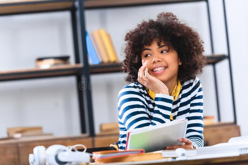 portrait of dreamy african american student looking away while stock photography
