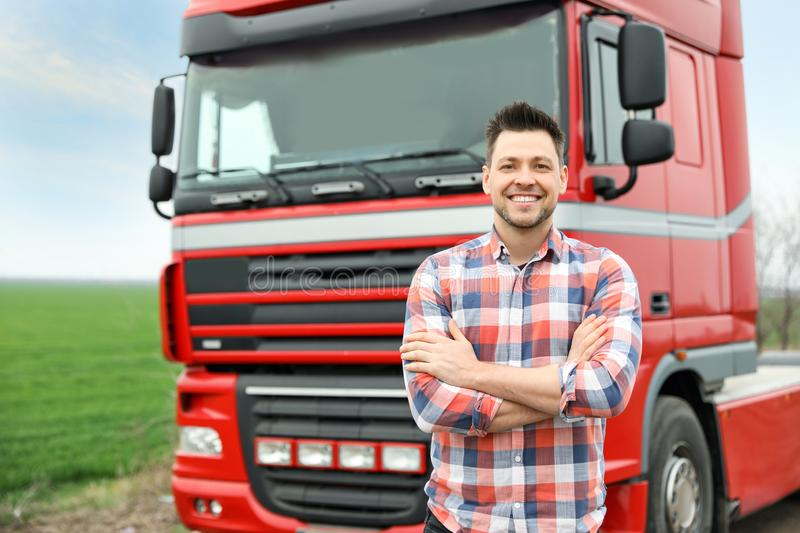 Portrait of driver at modern truck. Outdoors stock photo