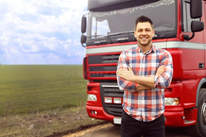 Portrait of driver at modern truck outdoors. Space for text stock photography