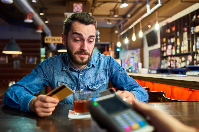Drunk Man Paying via Credit Card in Pub. Portrait of drunk young man paying via credit card buying drinks in bar with bartender handing payment terminal royalty free stock photo