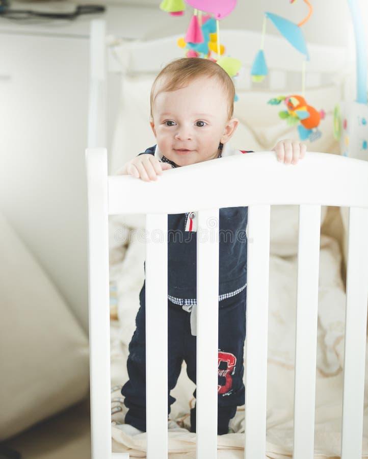 Portrait du bébé garçon de 1 an adroable se tenant dans la huche en bois blanche images libres de droits