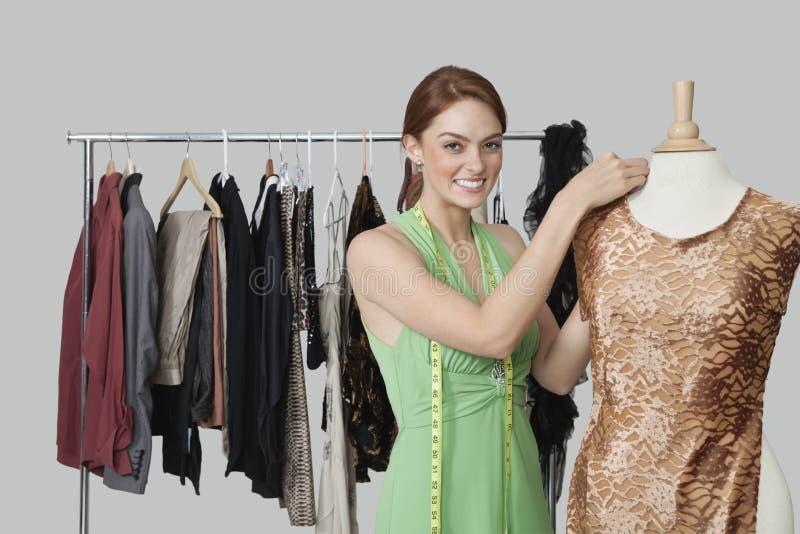 Portrait du beau couturier féminin ajustant le tissu sur le simulacre du tailleur image libre de droits