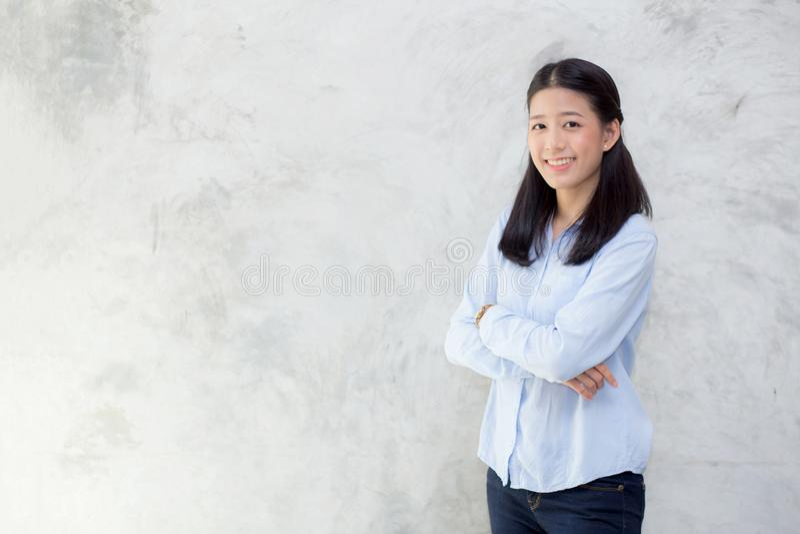 Portrait du beau jeune bonheur asiatique de femme se tenant sur le fond grunge de mur de texture grise de ciment images libres de droits