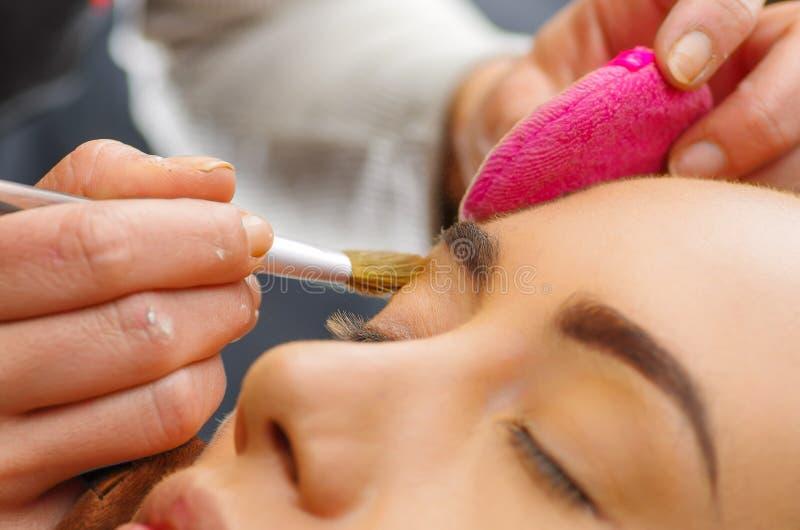 Portrait du beau visage de la jeune femme obtenant le maquillage L'artiste applique le fard à paupières sur son sourcil avec la b image stock