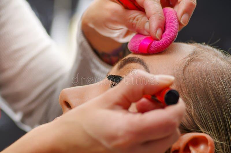 Portrait du beau visage de la jeune femme obtenant le maquillage L'artiste applique le mascara d'oeil sur ses yeux La dame images stock