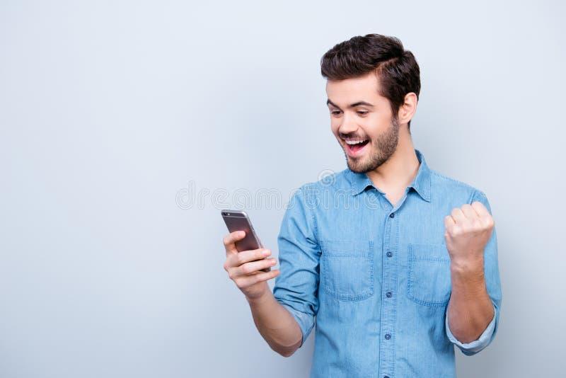 Portrait du brun hansome très heureux lisant un message sur son p photo libre de droits