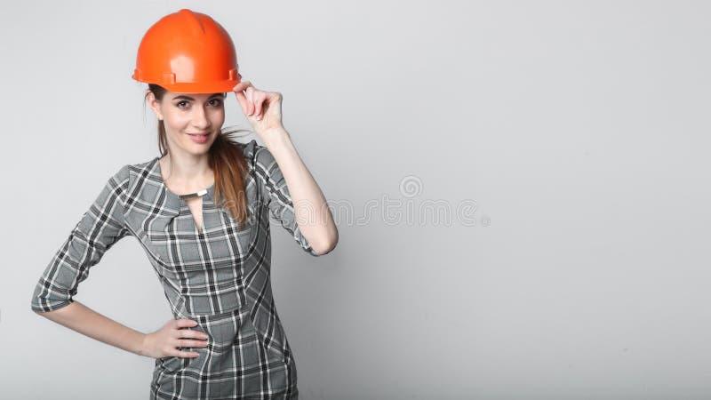 Portrait du casque de port de sourire de constructeur de femme d'affaires d'isolement sur le blanc photo libre de droits