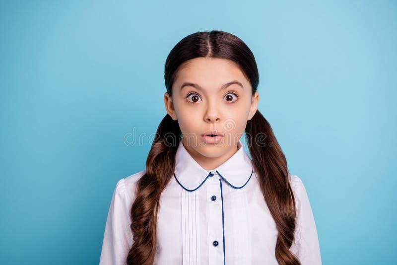 Portrait du chemisier blanc effrayé d'usage de stupeur de regard fixe d'enfant d'isolement au-dessus du fond bleu image libre de droits