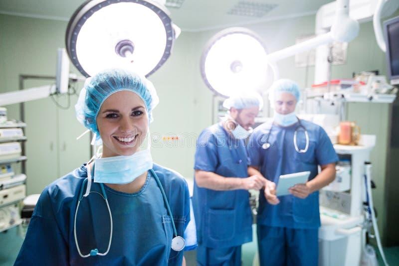 Portrait du chirurgien féminin de sourire tenant la pièce en fonction photographie stock