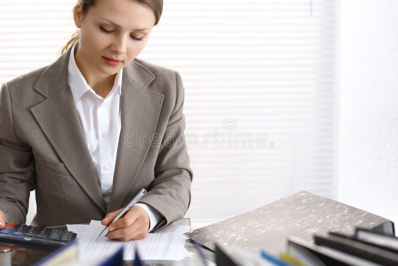 Portrait du comptable féminin ou de l'inspecteur financier rédigeant le rapport, calculant ou vérifiant l'équilibre Copiez la zon image stock