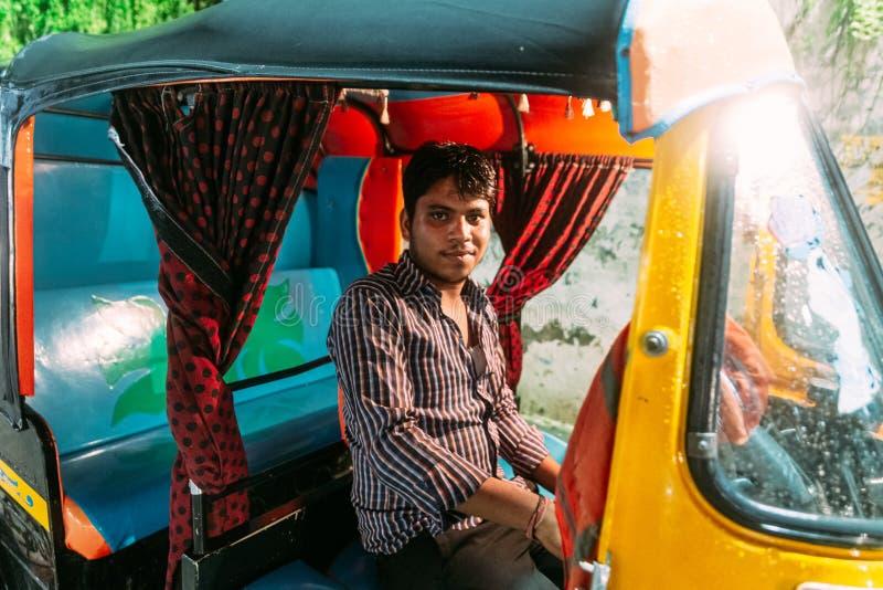 Portrait du conducteur de voiture jaune indien de pousse-pousse se reposant dans la voiture tout en pleuvant à Varanasi, Inde photographie stock
