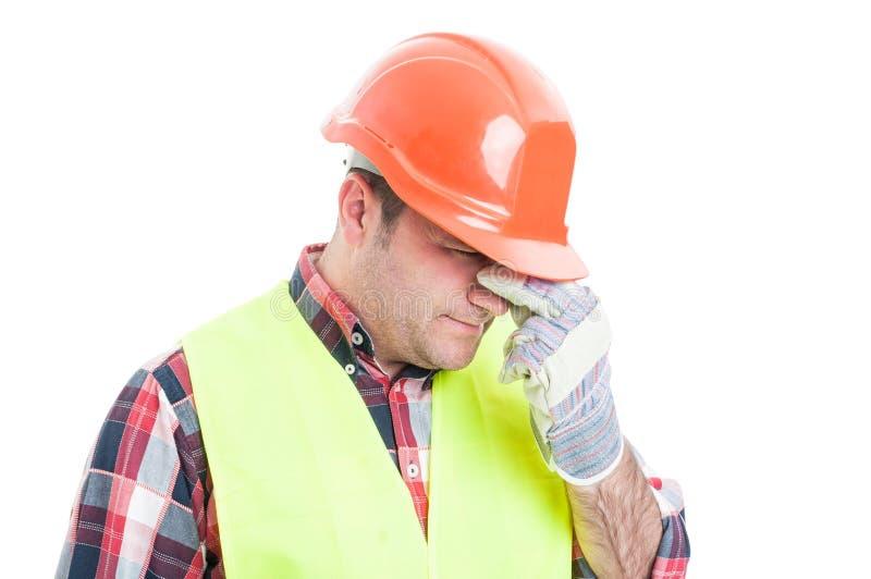Portrait du constructeur masculin soumis à une contrainte semblant bouleversé images stock