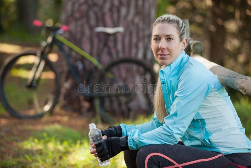 Portrait du cycliste féminin de montagne tenant la bouteille d'eau photographie stock libre de droits