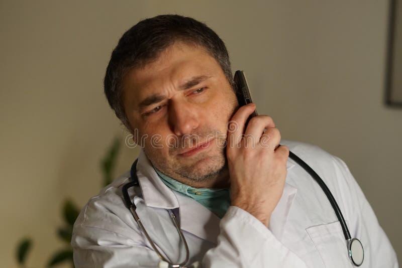 Portrait du docteur absorbé parlant à son téléphone portable image libre de droits