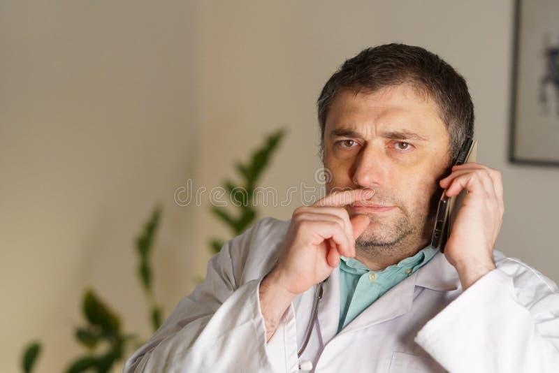 Portrait du docteur absorbé parlant à son téléphone portable images stock