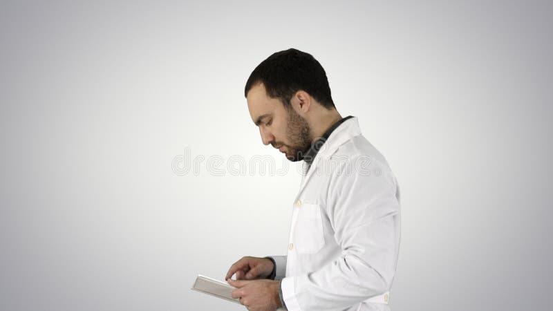 Portrait du docteur masculin marchant et à l'aide du comprimé numérique sur le fond de gradient image libre de droits