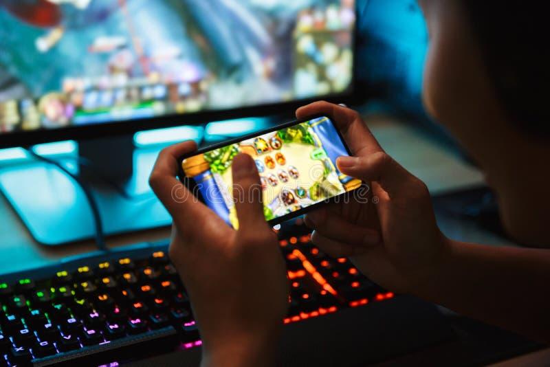 Portrait du garçon adolescent de gamer jouant des jeux vidéo sur le smartphone photographie stock