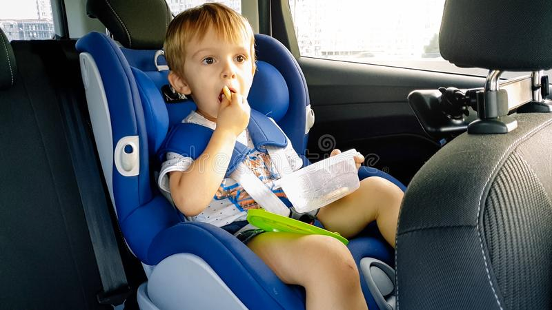 Portrait du garçon adorable d'enfant en bas âge s'asseyant dans le siège de sécurité de voiture d'enfant et mangeant des biscuits photos libres de droits