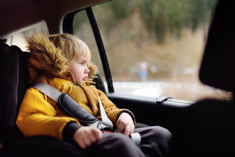 Portrait du garçon assez petit s'asseyant dans le siège de voiture pendant la promenade en voiture ou le voyage images libres de droits