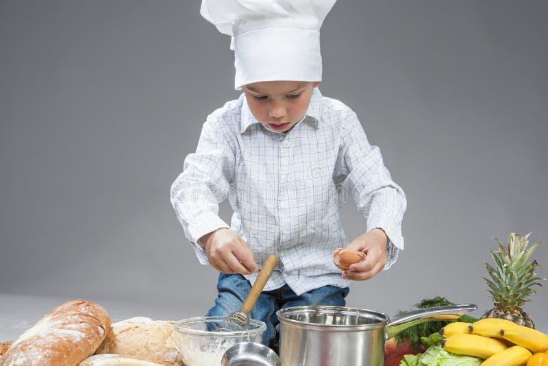 Portrait du garçon caucasien concentré mélangeant l'oeuf frais dans la casserole Pose en faisant cuire le chapeau photographie stock libre de droits