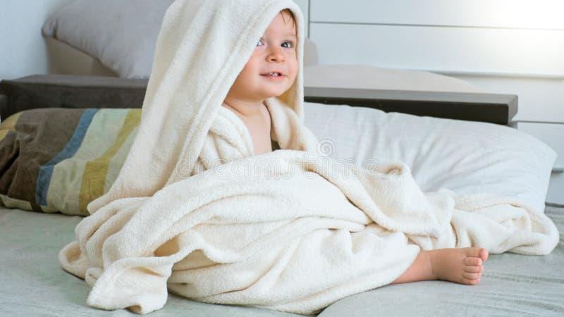Portrait du garçon de 1 an mignon d'enfant en bas âge s'asseyant sous la grande serviette ayant ensuite le bain photos stock