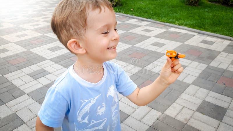 Portrait du garçon gai de sourire heureux d'enfant en bas âge courant en parc et tenant le petit hélicoptère de jouet Émotions po images stock