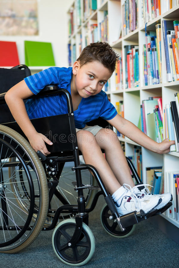 Portrait du garçon handicapé recherchant des livres dans la bibliothèque images libres de droits