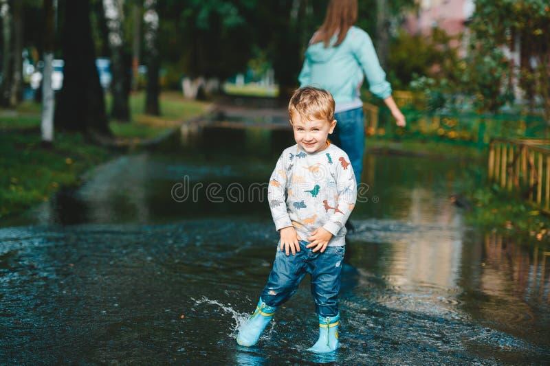 Portrait du garçon mignon d'enfant jouant dans un magma dans le kyard Sa mère sur un fond image stock