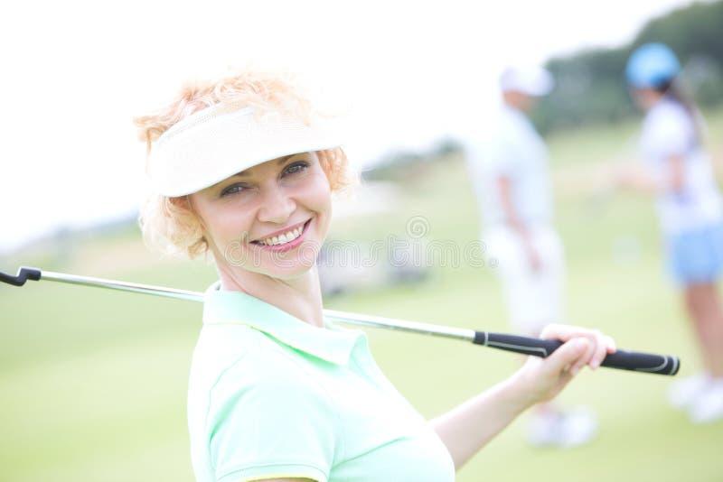 Portrait du golfeur féminin heureux tenant le club de golf images libres de droits