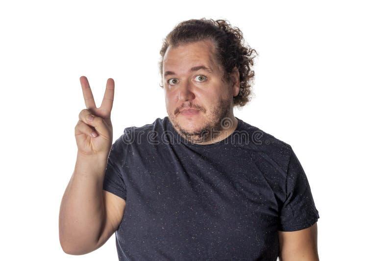 Portrait du gros homme drôle montrant le v-signe de paix ou le geste de victoire photo stock