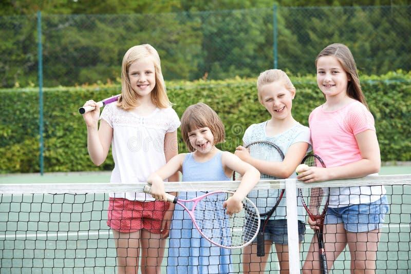 Portrait du groupe de filles jouant au tennis sur la cour photos stock