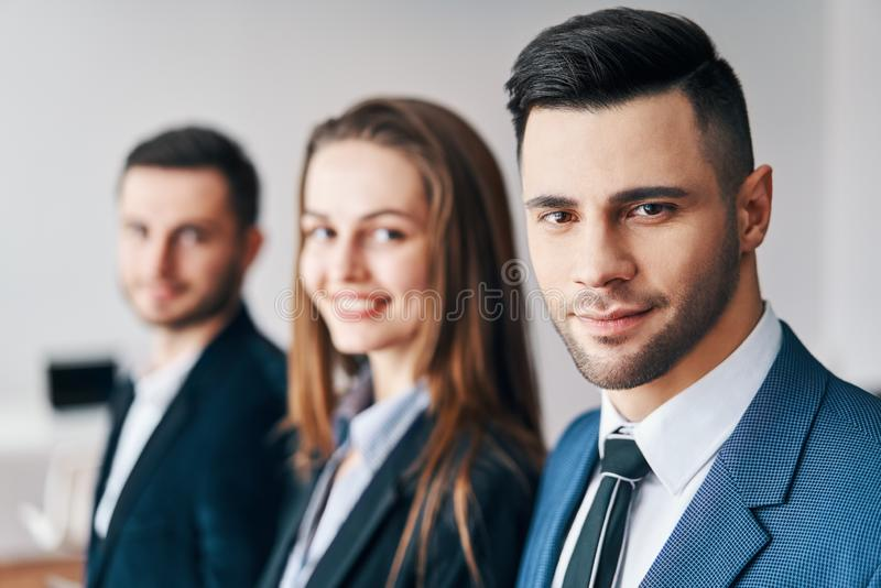 Portrait du groupe de jeunes hommes d'affaires dans une rangée dans le bureau images libres de droits