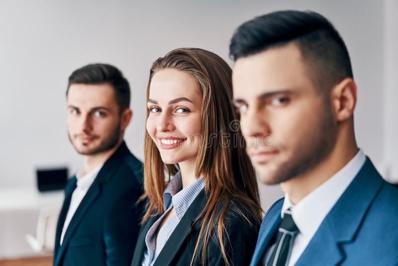 Portrait du groupe de jeunes hommes d'affaires dans une rangée dans le bureau photo stock