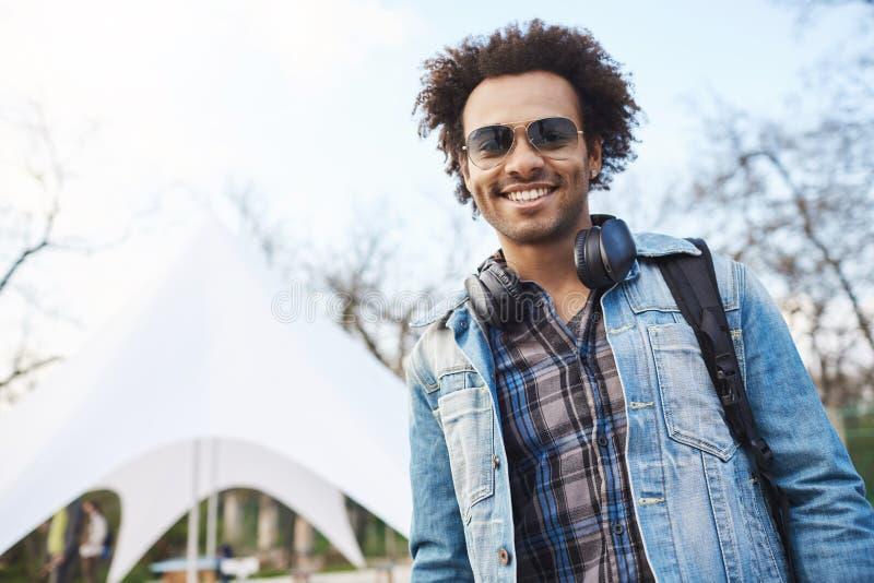 Portrait du jeune étudiant beau d'afro-américain avec la coiffure Afro souriant à l'appareil-photo, manteau de port de denim et photographie stock
