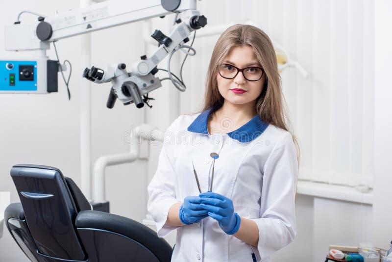 Portrait du jeune beau dentiste féminin tenant les outils dentaires au bureau dentaire moderne photo libre de droits